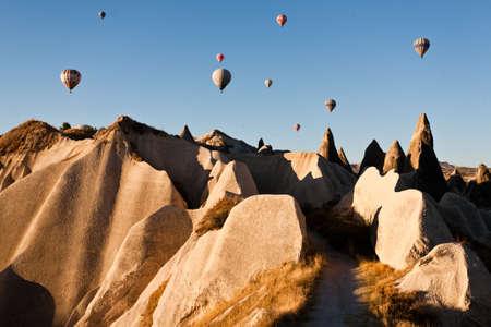 Hot air balloon over rock formations in Cappadocia, Turkey Stock Photo - 12835230