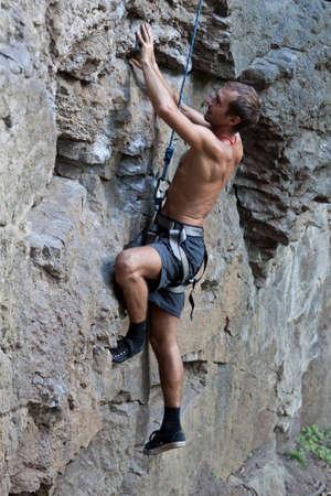 Skalní lezení v přírodě s lanem.
