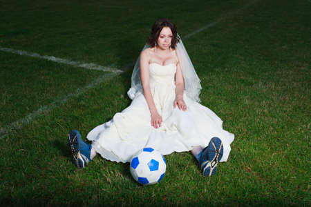 Beauty bride on a soccer field, wearing football boots and white dress  photo