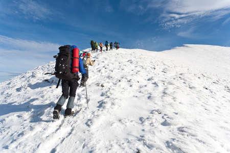 Skupina turistů pohybujících se na vrchol v zimních horách. Reklamní fotografie