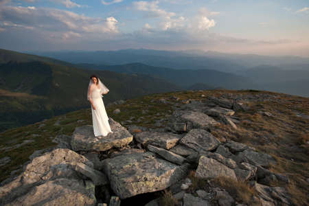Bride in wedding dress standing high in mountains. photo