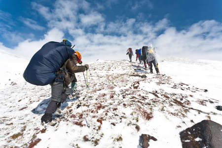 Turisté pohybující se v zasněžené Kamčatce, Rusko.
