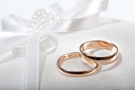 Two wedding rings with white flower in the background. Stock Photo