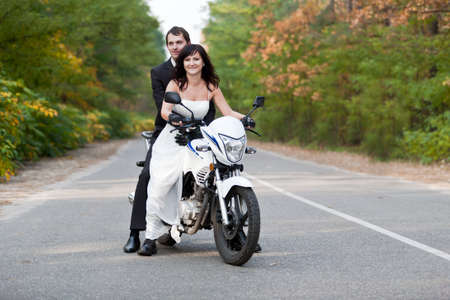 Wedding couple having fun on motorcycle.