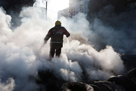 KIEV, UKRAINE - 23 JANUARY 2014: Firefighters extinguish a fire at the Independence square during Ukrainian revolution on January 23, 2014 in Kiev, Ukraine. Redakční
