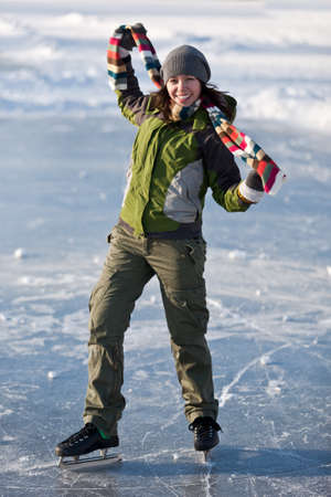 Cheerful girl having fun in winter ice skating. photo