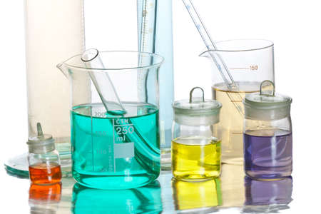 Volumetric laboratory glassware containing colored liquids isolated over white background photo
