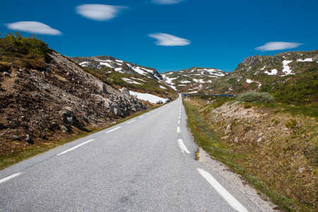 Norway landscape with lonely road and deep blue sky.