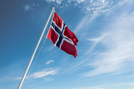 flagging: Flag of Norway on the blue sky background.