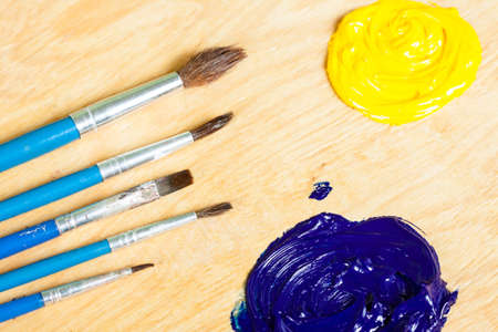 Palette with oil paint and brushes, macro view. Stock Photo