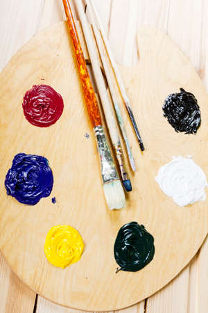 Palette with oil paint and brushes, on the wooden background. photo