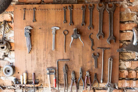 durty: Old vintage tools hanging on a wooden clipboard, hobby time in garage.