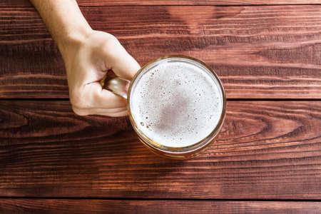 Muž ruce se sklenicí piva, hospody interiéru. Reklamní fotografie
