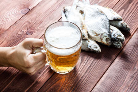 drunkenness: Male hand with a glass of beer and dried fish, traditional russian snack. Wooden background.
