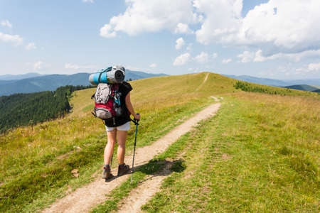 aim: Hiker with backpack relaxing on top of a mountain and enjoying valley view.