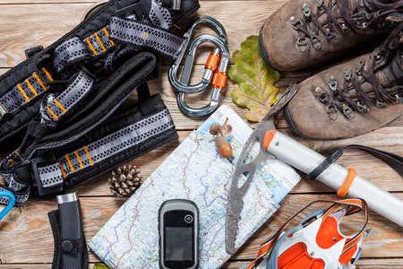 Ausrüstung für das Bergsteigen und Wandern auf hölzernen Hintergrund. Standard-Bild