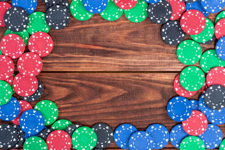 looser: Poker chips over old wooden table. Frame of poker chips. Casino background. Stock Photo