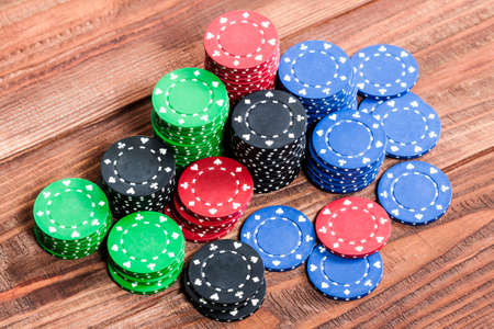 looser: Poker chips over old wooden table. Group of different poker chips. Casino background.