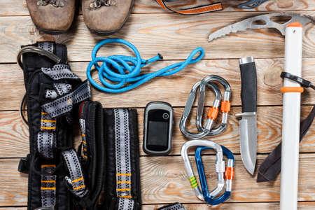 Ausrüstung für das Bergsteigen und Wandern auf hölzernen Hintergrund.