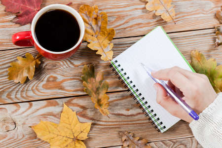 Coffee cup, notebook and autumn leaves on wooden background. Autumn and business background.