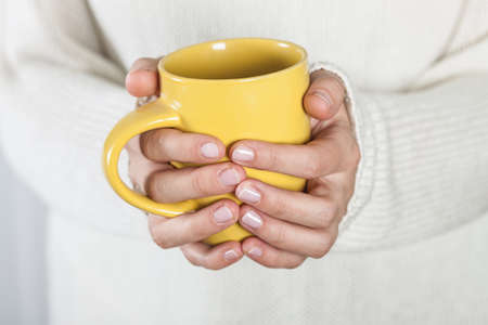 women holding cup: Cup of tea or coffee in female hands close up. Cold weather concept.