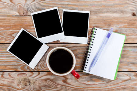 note paper: Workspace with coffee cup, instant photos, note paper and notebook on old wooden table. Business concept.