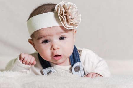 ojos hermosos: La muchacha hermosa bebé recién nacido con arco, tumbado en la cama y sonriendo. Foto de archivo
