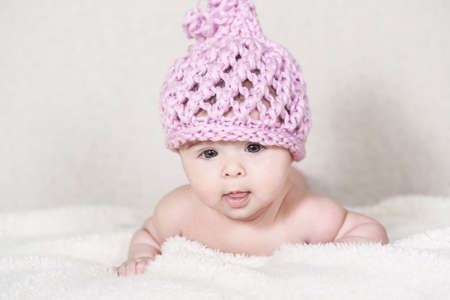 pink hat: Beautiful newborn baby girl with funny handmade pink hat, lying in her bed and smiling.