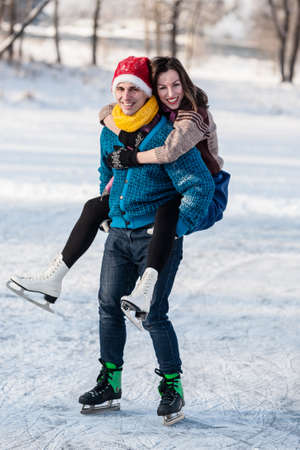 Happy couple having fun ice skating on rink outdoors. Winter sport and leisure concept. Love and fun in wintertime. Reklamní fotografie