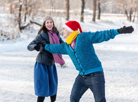 iceskates: Happy couple having fun ice skating on rink outdoors. Winter sport and leisure concept. Love and fun in wintertime. Stock Photo