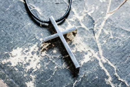 catholicism: Silver Christian cross on bible. Religious symbols concept. Stock Photo