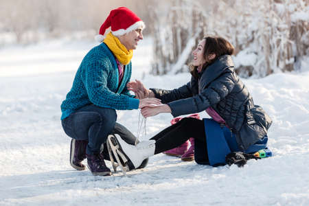leisure wear: Happy couple having fun ice skating on rink outdoors. Man helping to wear ice skates to his girlfriend. Winter sport and leisure concept. Love and fun in wintertime. Stock Photo