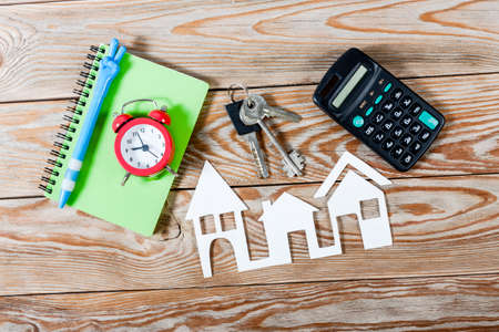 agency agreement: White paper house figure with keys, notebook, red alarm clock and calculator on wooden background. Real Estate Concept. Stock Photo