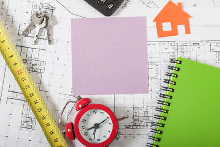 agency agreement: Model house on construction plan for house building, keys, red alarm clock and calculator. With pink blank business card. Real Estate Concept. Stock Photo