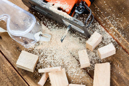 carpenter's sawdust: Electric jigsaw with many wooden bricks full of sawdust. On old scratched wooden table, work tools concept.