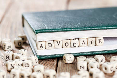 Advocate slovo napsané na dřevěné podložce v knize. Na starý dřevěný stůl.
