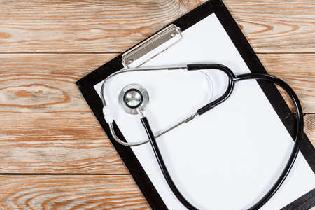 medical clipboard: Medical clipboard and stethoscope on wooden table background. Top view. Health care and medicine concept. Stock Photo