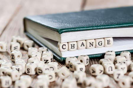 Change word written on a wooden block in a book. On old wooden table. Stok Fotoğraf