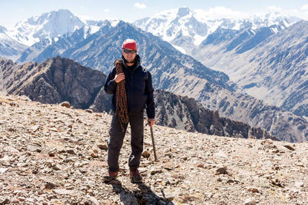 tien shan: Hiker relaxing on top of a mountain and enjoying valley view. Tien Shan mountains, central asia, Kyrgyzstan. Climbing and mountaineering concept.