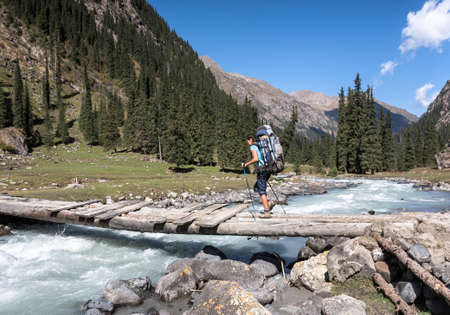 Hiker crossing river at Tien Shan mountains, central asia, Kyrgyzstan. Climbing and mountaineering concept.