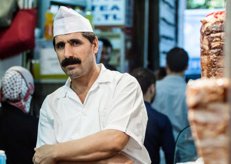 Istanbul, Turkey - September 6, 2011: Unknown man cooks and sells traditional kebab in a small buffet on streets of Istanbul.