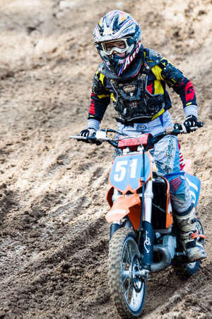Kiev, Ukraine - October 17, 2016: Kid on motorcycle going thru dirt, during Championship of Ukraine on cross-country final stage. Editorial