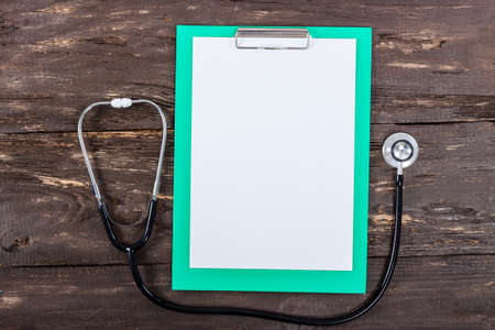 medical clipboard: Medical clipboard and stethoscope on old dark wooden table background. Top view. Health care and medicine concept. Stock Photo