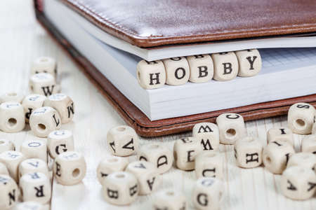 keywords adult: Word HOBBY written on a wooden block in a book. On old white wooden table. Stock Photo