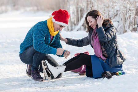 iceskates: Happy couple having fun ice skating on rink outdoors. Man halping to wear ice skates to his girlfriend. Winter sport and leisure concept. Love and fun in wintertime.