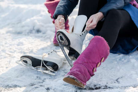 Happy girl wearing ice skates at a wintertime, on frozen pond. Winter sport and leisure concept.