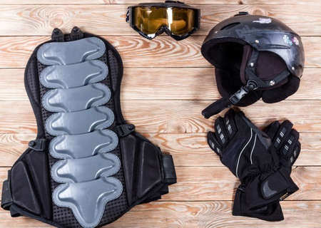 safety googles: Overhead view of ski and snowboard accessories placed on rustic wooden table. Items included helmet, goggles, gloves and back protection. Winter sport leisure time concept. Stock Photo