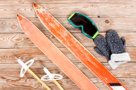 safety googles: Overhead view of retro ski accessories placed on old rustic wooden table. Items included old retro wooden ski, goggles, gloves and ski sticks. Winter sport leisure time concept. Stock Photo