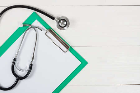 medicine background: Medical clipboard and stethoscope on white wooden table background. Top view. Health care and medicine concept. Stock Photo