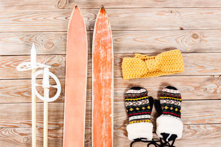 crosscountry: Overhead view of retro ski accessories placed on old rustic wooden table. Items included old retro wooden ski, goggles, gloves and ski sticks. Winter sport leisure time concept. Stock Photo
